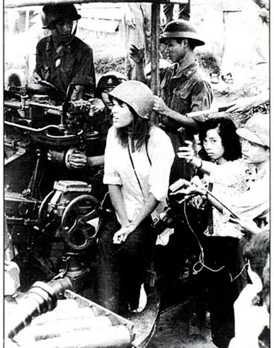 Jane Fonda sitting on anti-aircraft gun in Hanoi.